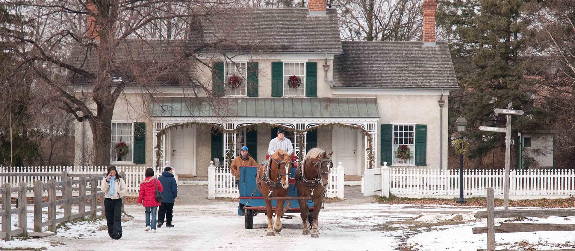 visitors to Black Creek Pioneer Village enjoy a horse drawn wagon ride at Christmas